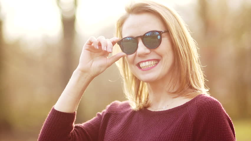 f30981369d51 Close up portrait of a beautiful young blonde in sunglasses. The girl  smiles sincerely, showing even white teeth. Early spring in the city park,  ...