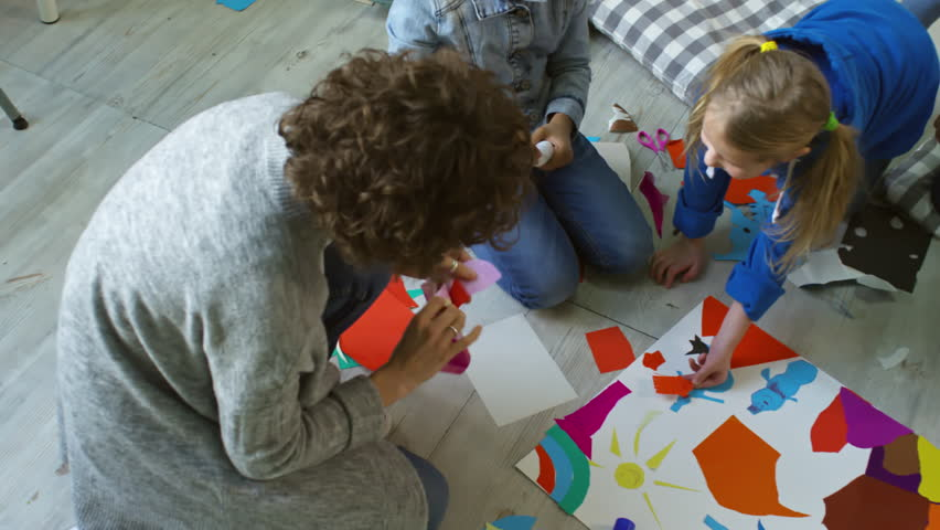 Top view of woman and little children sitting on floor, cutting out color paper and sticking pieces on sheet while doing collage in team