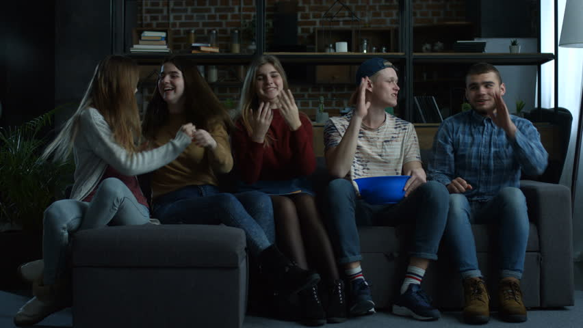 Happy football fans watching soccer on tv, cheerng for team and celebrating victory while sitting on the couch with popcorn in domestic room. Group of excited friends watch sport on television at home   Shutterstock HD Video #1008668875