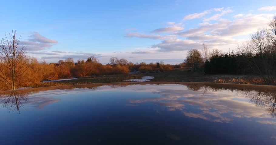 The reflection of blue sky, clouds and trees on the mirror surface, allowing the sun in the evening and dusk. Slow side-moving camera - 001   Shutterstock HD Video #1008681445