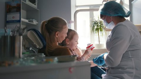 Girl, her mom and the dentist in the dental office, the stomatologist advising with a special toy