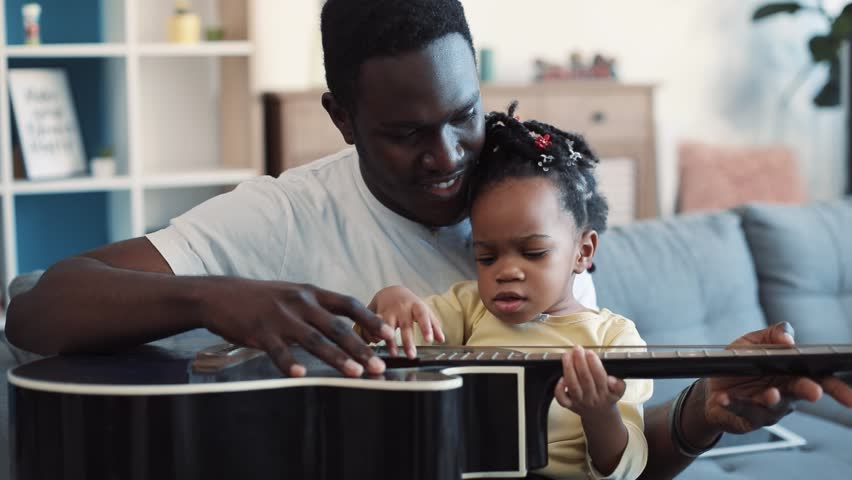 Smiling young father holds his little cute baby-girl on his knees and tries to teach her to play the guitar, cheerful toddler claps the guitar as if she playing it. Modern family, happy memories. Slow | Shutterstock HD Video #1008693205