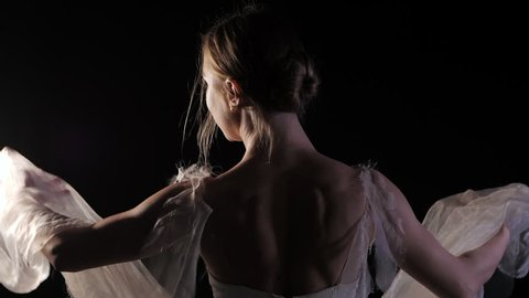 Ballerina is practicing her moves in dark studio. Young girl dancing with air white dress tutu, spinning around and smiling. Gracefulness and tenderness in every movement