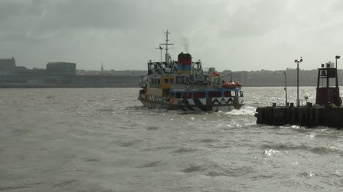 A Mersey Ferry leaves the Birkenhead port heading for Liverpool across the River Mersey Estuary.