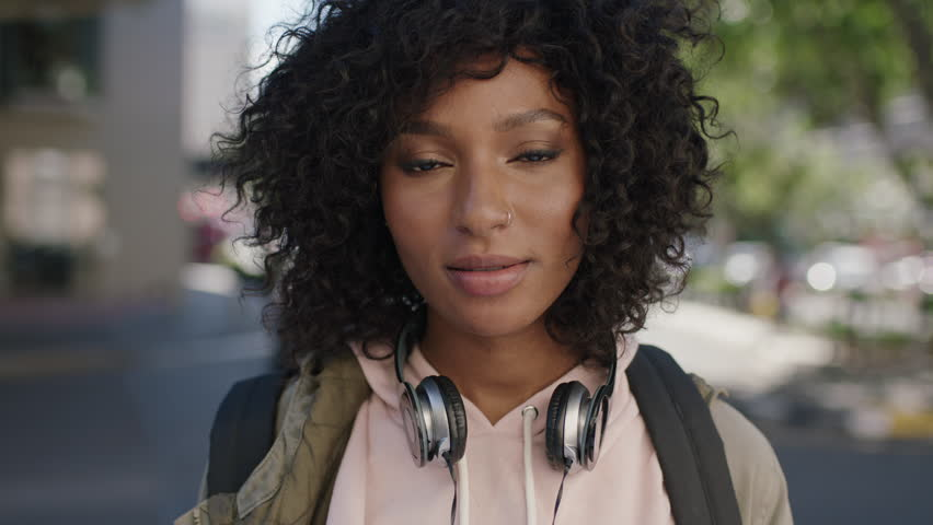 portrait of young attractive african american woman afro hairstyle smiling cheerful in city street wearing headphones urban lifestyle #1008745475