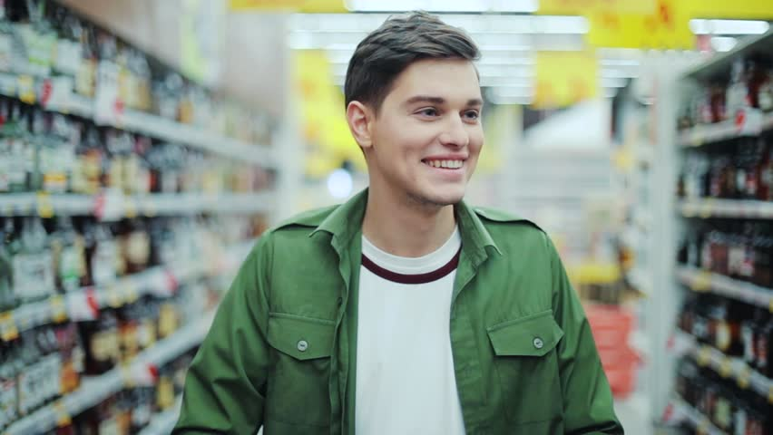 Close up smiling man walk with shopping cart at the supermarket feel happy hypermarket hand food shop store customer grocery handsome indoor lifestyle male market buyer guy product shopper slow motion