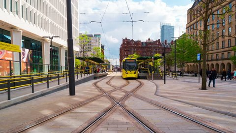 MANCHESTER, ENGLAND - MAY 20, 2017: Light rail yellow tram Metrolink in city center of Manchester, UK in the evening. The system has 77 stops along 78.1 km and runs through seven of the ten boroughs.