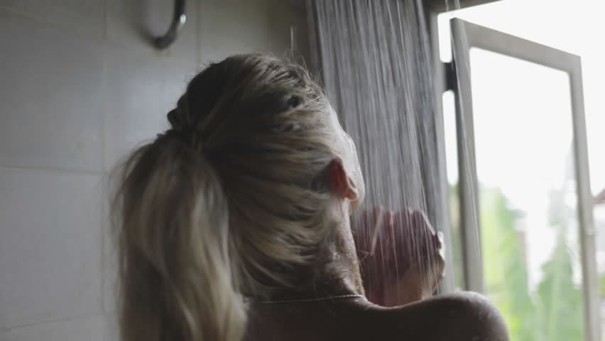Closeup blond attractive woman or girl refreshing her body in the shower, looking at the opened window, relaxing | Shutterstock HD Video #1008764675