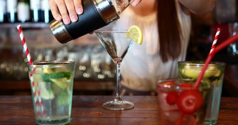 Mid section of barmaid pouring cocktail in glass at bar counter in pub