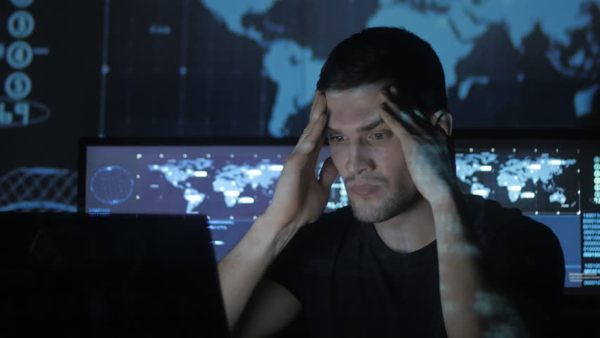 Young Man geek hacker overworking at computer and suffers from a headache in cyber security center filled with display screens. | Shutterstock HD Video #1008776765