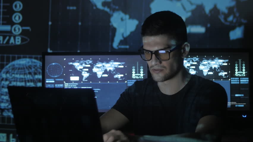 Portrait of a young programmer working at a computer in the data center filled with display screens | Shutterstock HD Video #1008776855