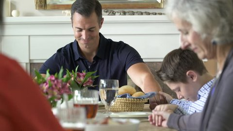 Family saying grace and making a toast at dinner table.