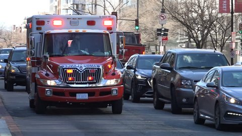 WASHINGTON, DC - MARCH 14, 2018: EMS ambulance in downtown traffic, passes close, siren and horn, through intersection on K Street, responding.  EMS is part of DC Fire & EMS, aka DCFEMS