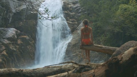backside view slim girl with long plaits in orange bikini sits on large log hanging above gorge against waterfall