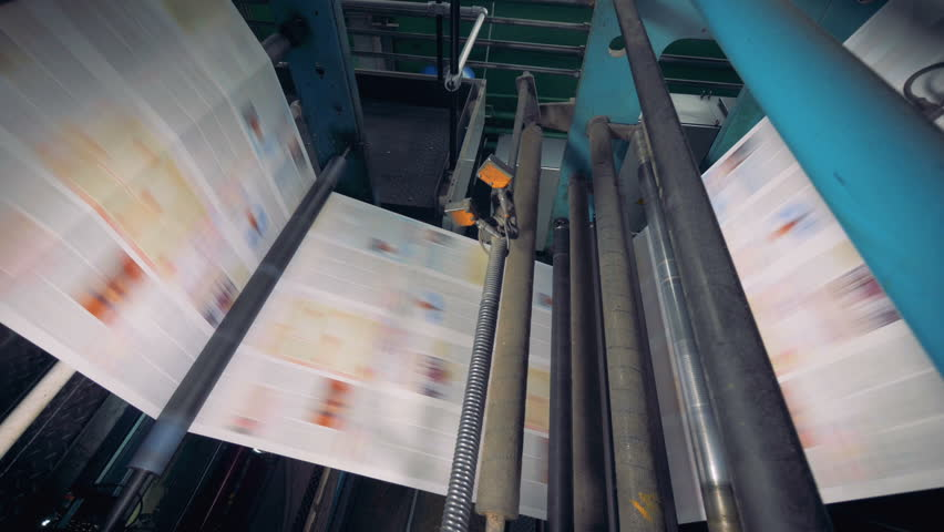 Conveyor with numerous freshly printed newspapers. 4K.