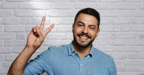 Portrait of happy Italian man smiling. Young man looking at camera and doing peace sign with hand or V sign with fingers.