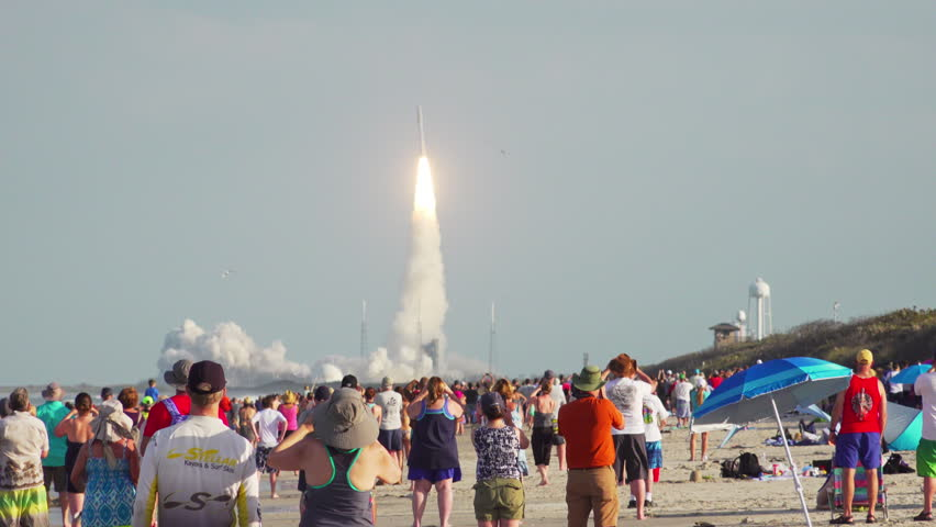 CAPE CANAVERAL, FLORIDA, March 2018 - Crowds of spectators on the beach watch a United Launch Alliance (ULA) Atlas 5 space rocket launch from Cape Canaveral, Florida Kennedy Space Center. 120 fps.