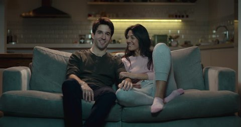 Happy couple enjoying a cozy night in on the sofa watching tv
