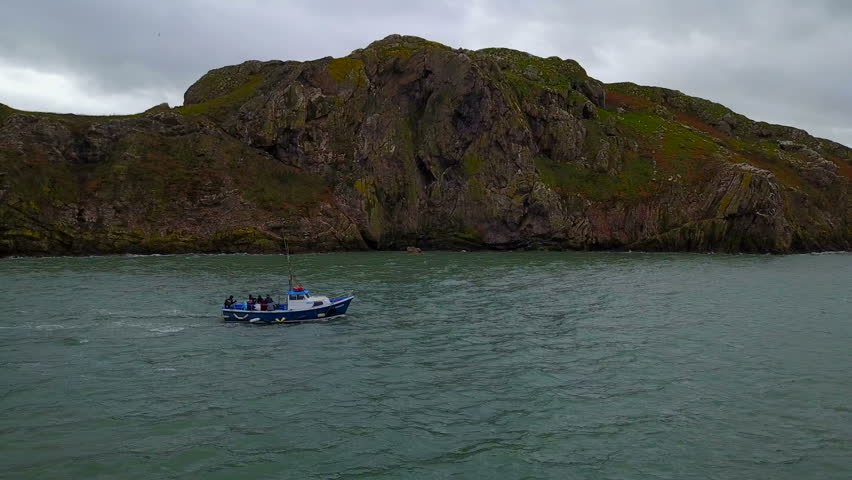 Aerial view of boat with unrecognizible people in sea sailing near the Ireland`s Eye island, Howth, Ireland   Shutterstock HD Video #1008874805