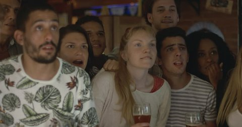 Sports enthusiasts celebrating victory while watching televised match in bar, slow motion
