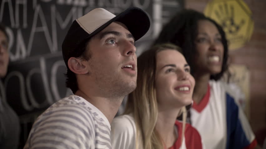 Football fans bonding while watching televised match at sports bar | Shutterstock HD Video #1008892445