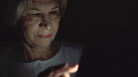 Lonely elderly senior woman relaxing at home reading news on smartphone. Secretly using mobile at night hiding from people. Dark only face illuminated. Loneliness privacy in technology era concept