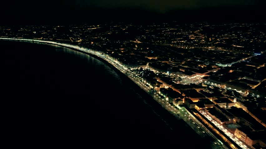 Night aerial view of sea and illuminated Nice town in France. Flight over promenade.
