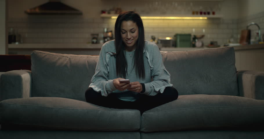 Girl sitting crossed legged on a sofa using her smartphone to chat with her friends online.