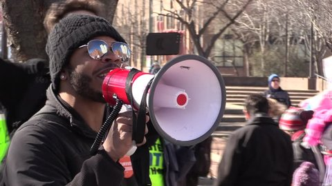 """Philadelphia, Pennsylvania / United States - March 24, 2018: Supporting the victims of the Parkland High School shooting, close shot, man with bullhorn leads crowd in a """"Stand up! Fight back!"""" chant."""