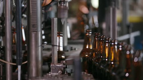 Electronics checks the quality of bottle on glass factory. Sorting beer bottles. Quality control of glass bottles. Technological line for bottling of beer in brewery. Beer bottle factory. Close up.