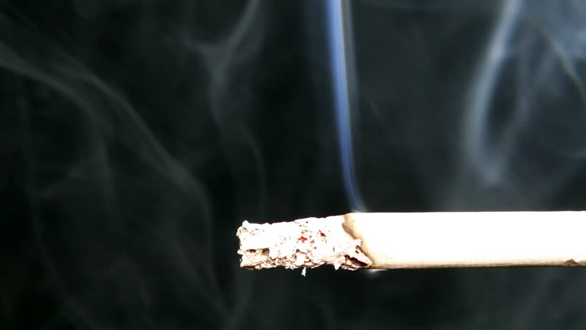 Smoking cigarette on a black background. The smoke in the backlight is clearly visible. | Shutterstock HD Video #1008999545