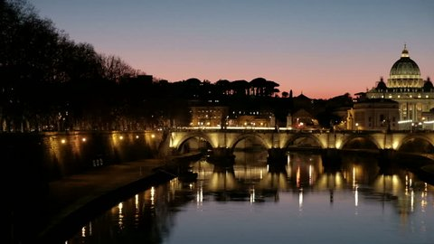 Riverbank camera panning right revealing Ponte Sant'Angelo, distant St. Peter's Basilica in Vatican City illuminated by night lights at dusk blue hour in Rome, Italy.