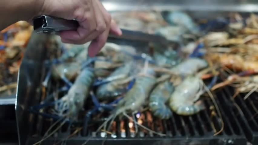 Grilled giant river prawn or big shrimp on charcoal stove, Barbecue seafood party, Traditional Thai food recipe.