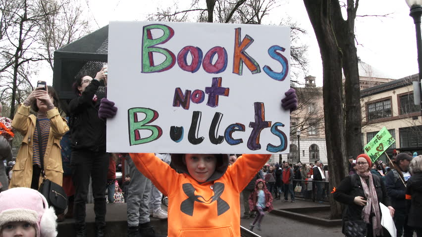 "PORTLAND, OREGON / USA - MARCH 24, 2018: Little boy holds sign reading ""Books, Not Bullets"" joining in the March For Our Lives protesting gun violence and school shootings."