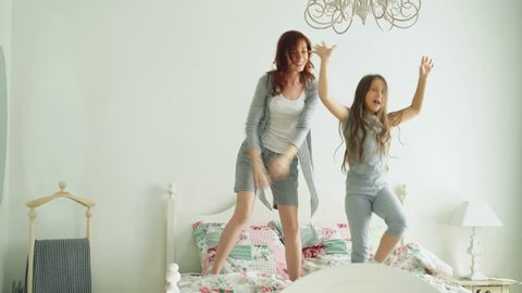 Funny little girl with her loving mother have fun learning dance modern style together watching dancing show on TV and jumping on bed during morning at home