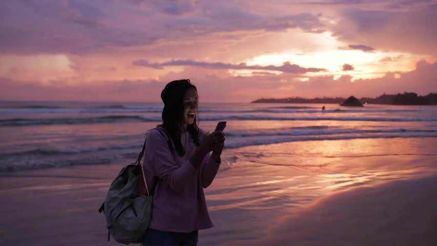 Girl types a message near ocean at sunset. | Shutterstock HD Video #1009073495