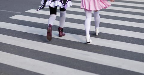 Japanese female friends running across crossing, Harajuku, Tokyo, Japan