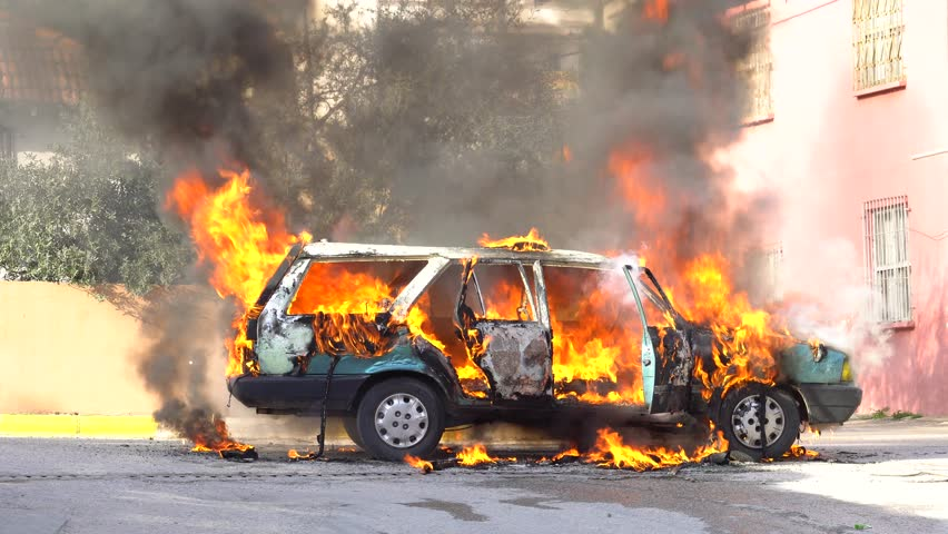 An abandoned import car on fire burns and later has something small explode while the horn blares. | Shutterstock HD Video #1009114985