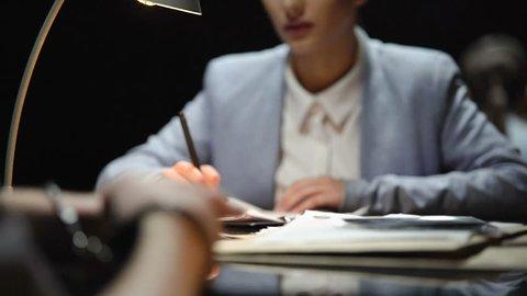 Female defense attorney interrogating nervous suspect, writing his testimony