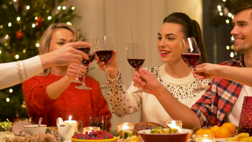 Holidays and celebration concept - happy friends having christmas dinner party at home, drinking red wine and clinking glasses