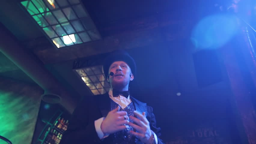 A young magician in a black hat and costume performs on stage. Slow motion.