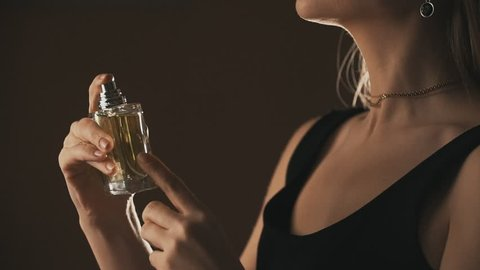Sensual girl spraying fragrance in slow motion, with scent particles. Concept of sensual feminine scent.