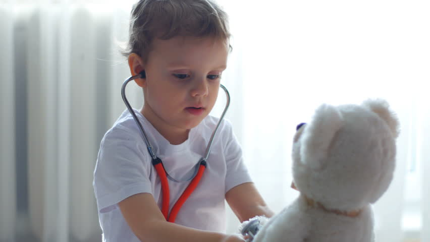 Baby with doctor's tools playing with teddy bear