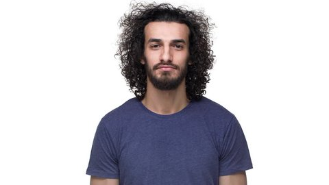 Closeup portrait of hairy muscular man 25y in casual gray t-shirt nodding and expressing approval with smile, over white background. Concept of emotions