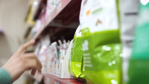Man choose feed for his dog in pet shop