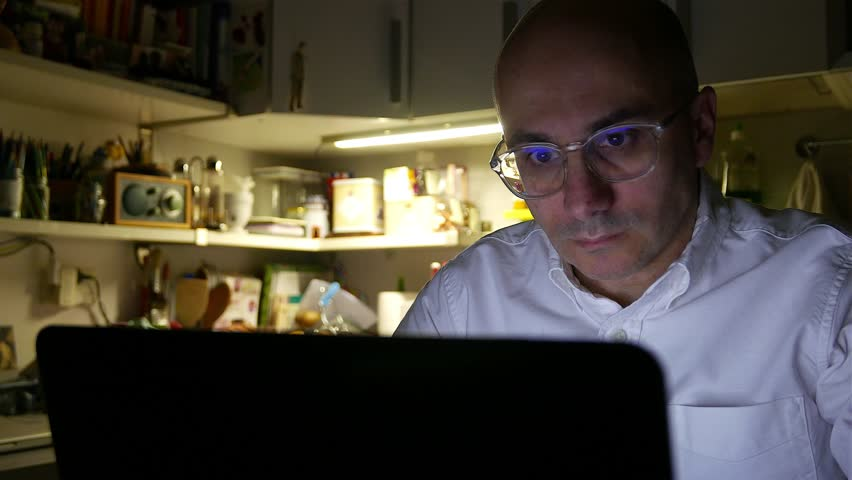 Man surfing the web with laptop at home during night time.