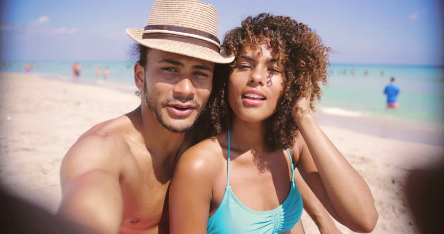 Laughing happy ethnic young man and woman looking at camera and taking selfie on sandy beach at the ocean.   Shutterstock HD Video #1009188395