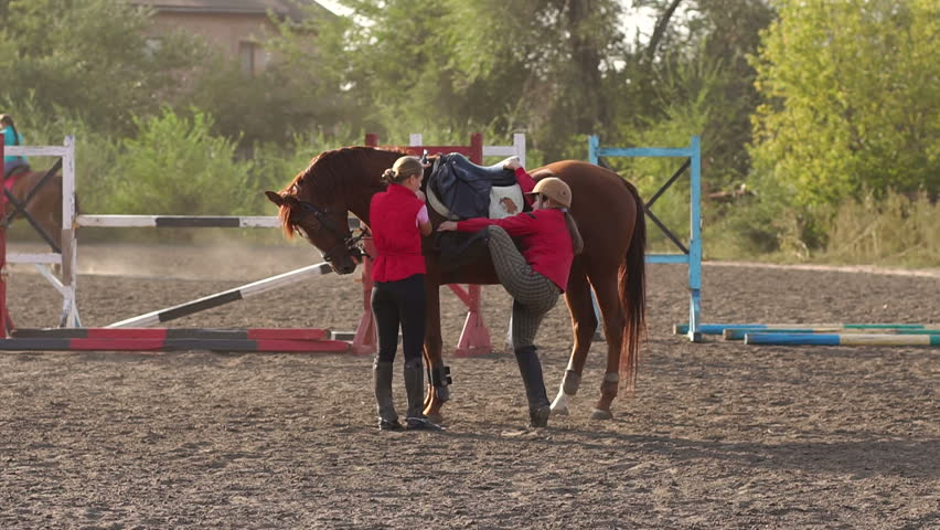 A female coach helps a child to climb a horse, learning to ride a horse at a horse farm. Children are engaged in horse riding. Slow motion.