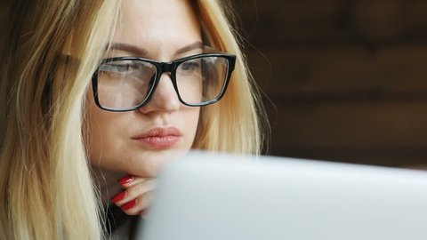 closeup portrait of female person using portable computer laptop looking monitor sad worried emotional face checking news hipster glasses blond woman internet business project manager browser connect