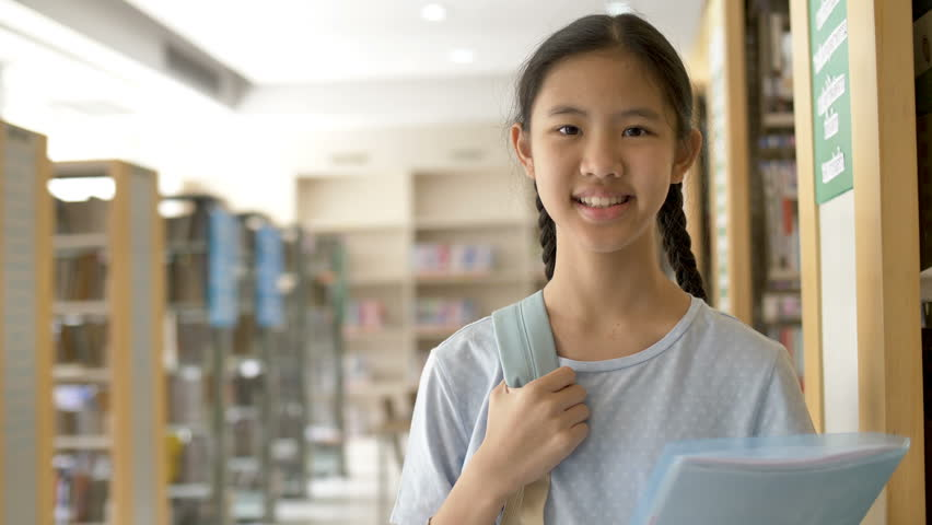 4K Asian teenager student holding books and backpack in school library for inspiration,Shoot wit natural light, Slow motion shot